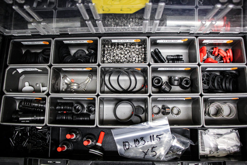 A black storage bin is open and divided into smaller compartments by grey dividers. Each small block holds a piece of the scuba equipment.